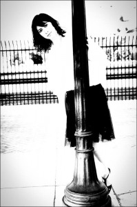Black and white photo of a young woman peering around a streetlamp