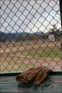 A baseball glove behind a fence in the dugout