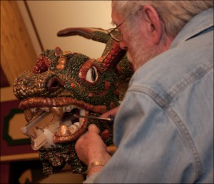 A older man carving a carousel creature