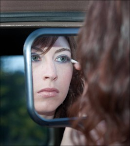A woman putting on makeup using a rearview mirror