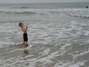 A young boy standing in the ocean