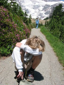 A boy crying on a trail as Mom continues with the hike