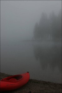 A kayak near a still  lake shrouded in fog